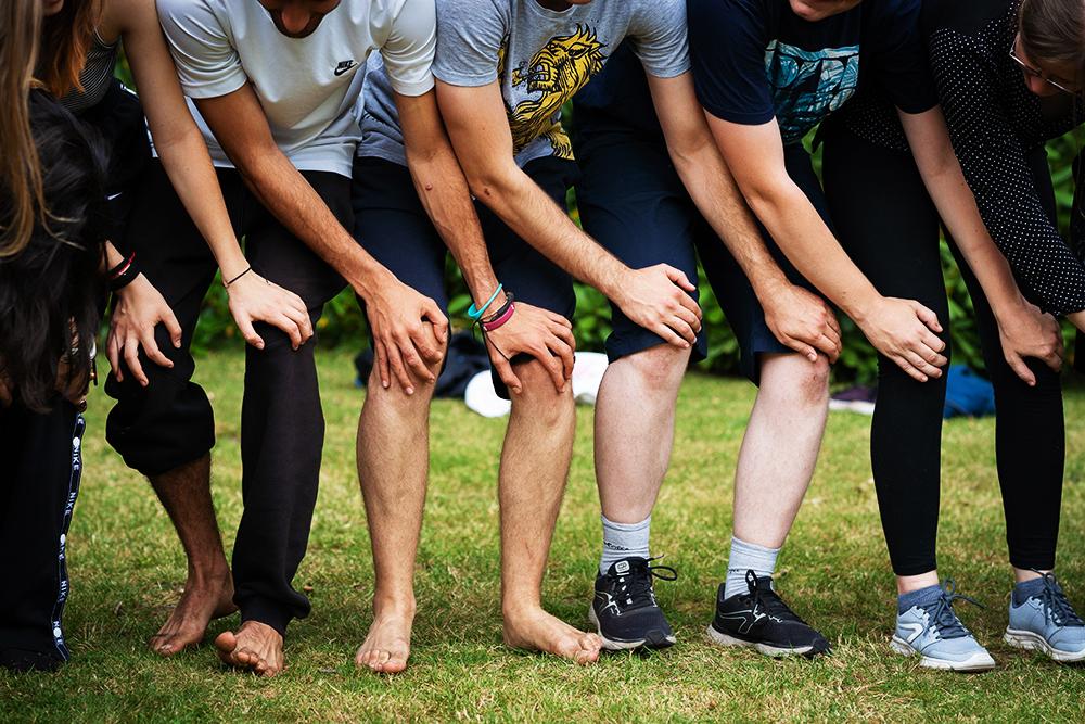 Jongeren met handen over knieën. Foto Liesbet Sanders